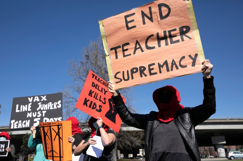 A group of anonymous demonstrators calling themselves Guerrilla Momz protest against school closures during a rally to open schools for in-person instruction at Astro Park in Oakland on Feb. 28, 2021. Photo by Anne Wernikoff, CalMatters