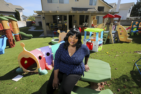 Cynthia Bassett stands for a portrait in her backyard in San Bernardino on March 16, 2021. Cynthia has been running a daycare at her house for 22 years. Photo by Shae Hammond for CalMatters