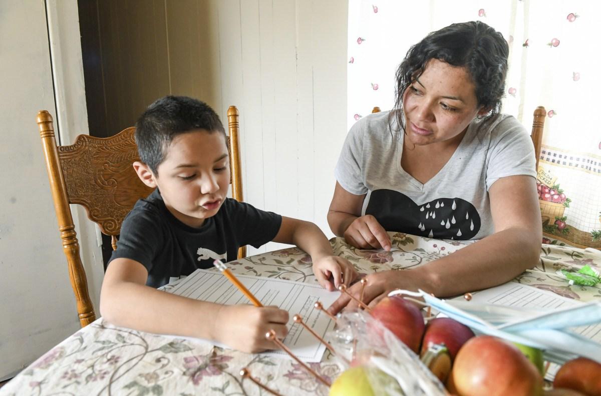 Carolina Navarro, de 34 años, ayuda a su hijo César Alejandro con la tarea en su casa móvil en Cantua Creek el martes 2 de marzo de 2021. Navarro está divorciada, tiene dos hijos y no tiene trabajo desde noviembre.
