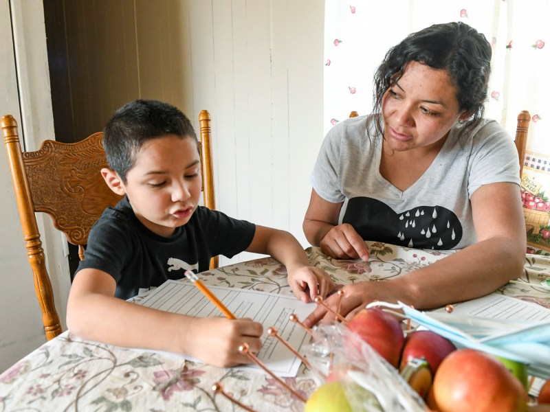 Carolina Navarro, 34, helps her son Cesar Alejandro with his homework at their mobile home in Cantua Creek on March 2, 2021. Navarro is divorced with two children and has been out of work since November. Photo by Craig Kohruss, The Fresno Bee
