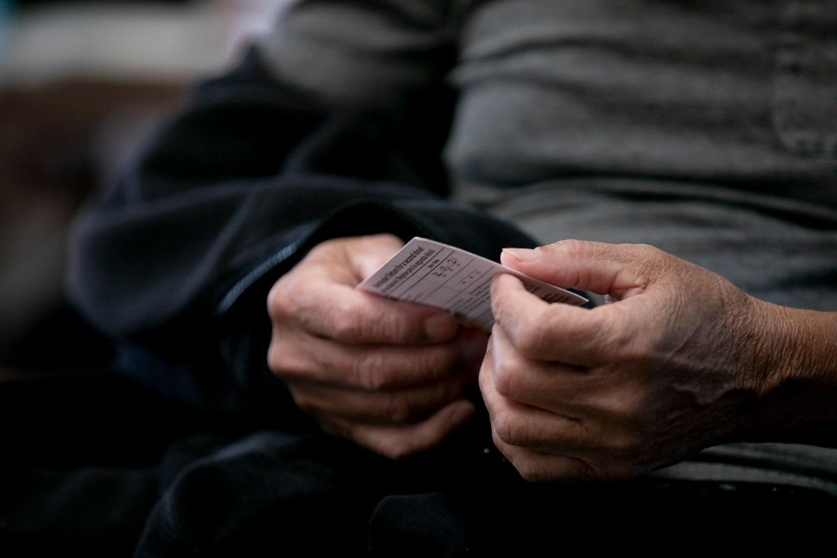 Domingo Comin, un empleado de Carefield Assisted Living en Castro Valley, sostiene su tarjeta de vacunación. Los funcionarios de salud de Californa dicen que no tienen planes de desarrollar un pasaporte estatal de vacunación. Foto de Anne Wernikoff, CalMatters