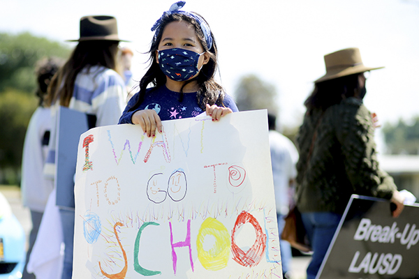 Olivia Garcia protests for schools to reopen at Ted Watkins Park in Watts on March 13, 2021. Photo by Shae Hammond for CalMatters