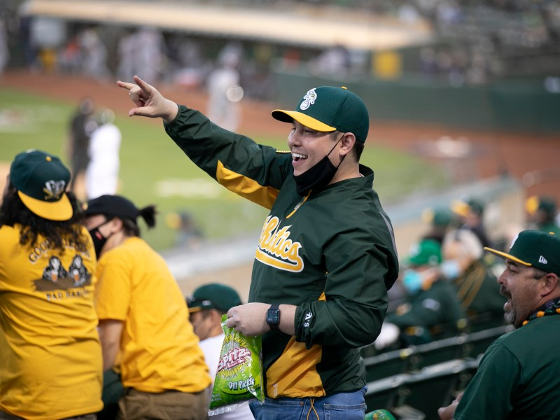 Lifelong Oakland Athletics fan Kurt Samuels cheers for a young boy who caught a fly ball several rows away during the season opener against the Houston Astros at Oakland Coliseum on April 1, 2021. Major League Baseball opened for in-person games for the first time since October 2019. Photo by Anne Wernikoff, CalMatters