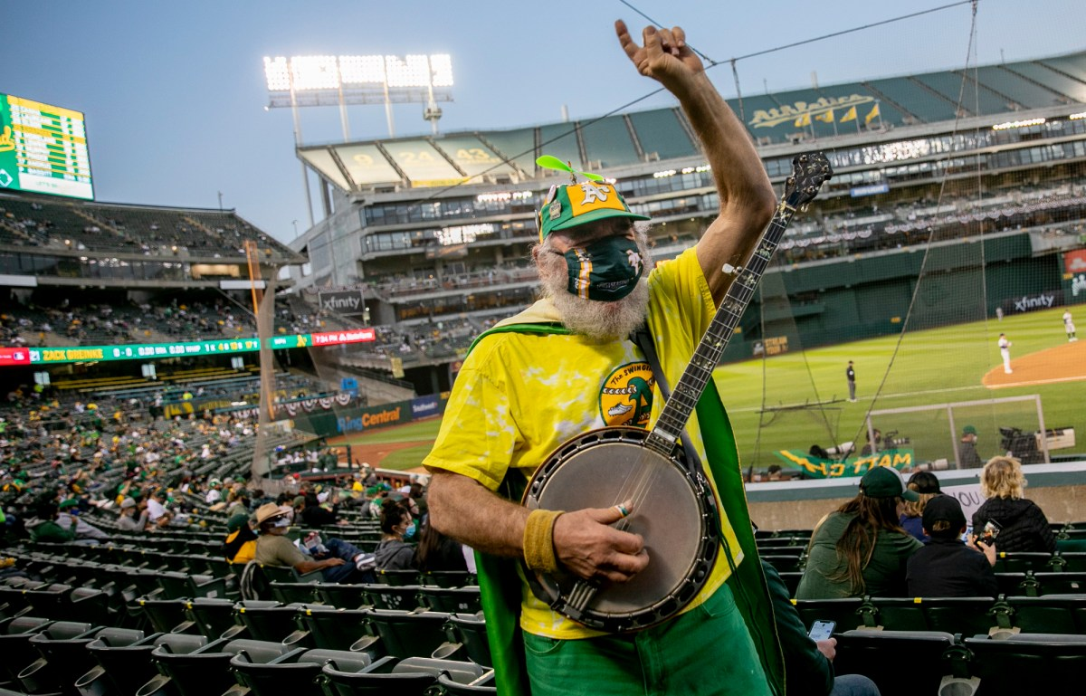 "San Francisco resident Stacy Samuels, also known as Super A or Banjo Man, plays the banjo while cheering in the stands. Samuels, who has been bringing his banjo to Athletics games for more than 30 years, said ""It's great. It feels like a regular game,"" of the season opener. Photo by Anne Wernikoff, CalMatters"