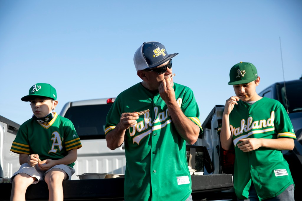 "Ernie Robles, center, enjoys chicken wings in the parking lot with his sons Benicio, left, and Antonio, right, before entering the stadium for the start of the game. ""Once I get in I'll put my mask on. It's the new, new, you know?"" He said of the new safety protocols. Photo by Anne Wernikoff, CalMatters"