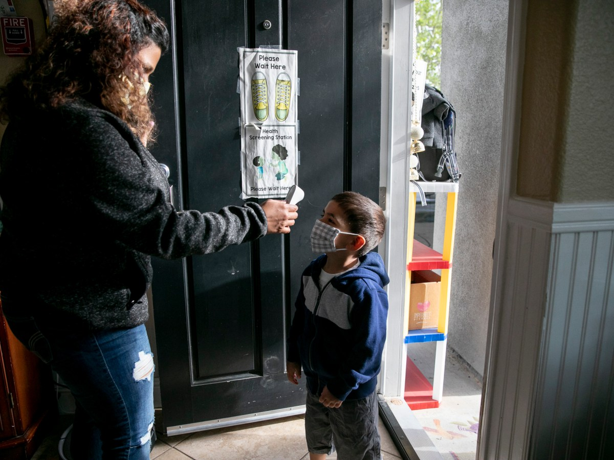 Jesse Hamblen, 3, has his temperature checked by Shruti Agarwal he arrives in the morning to her home-based daycare center in Livermore on April 13, 2021. Photo by Anne Wernikoff, CalMatters