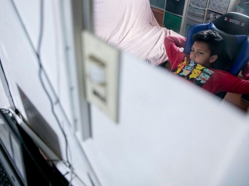 Mario Ramírez García, de 10 años, escucha mientras su maestro se dirige a la clase durante el aprendizaje a distancia en el dormitorio que comparte con su hermana el 23 de abril de 2021. Según su padre, la conexión a Internet en su casa de Oakland se corta aproximadamente dos veces por semana, lo que es especialmente frustrante para los niños cuando están tomando exámenes. Foto de Anne Wernikoff, CalMatters
