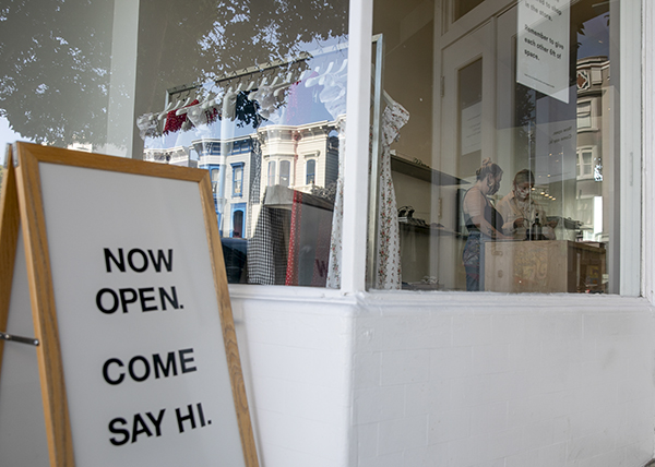 A sign welcoming customers at Reformation in the Mission neighborhood of San Francisco on July 25, 2020. Gov. Newsom has announced June 15 as the target for businesses to reopen without restriction. Photo by Anne Wernikoff, CalMatters