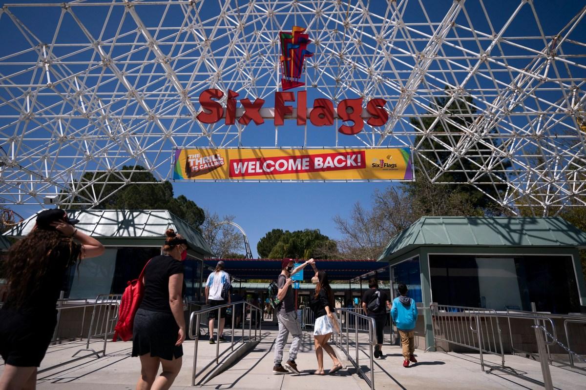 """Dos visitantes bailan debajo de un letrero de """"Bienvenido de nuevo"""" en Six Flags Magic Mountain en su primer día de reapertura para miembros y titulares de pases en Valencia el 1 de abril de 2021. Foto de Jae C. Hong, AP Photo"""