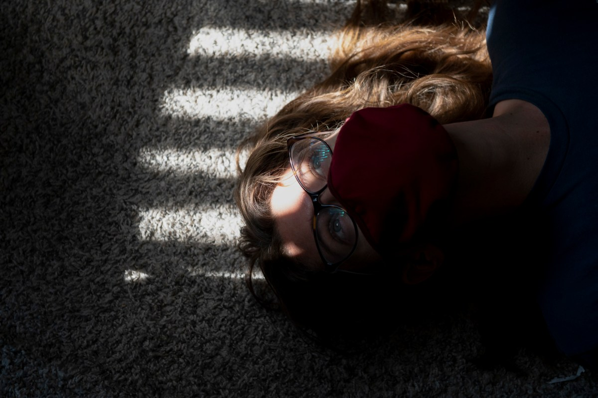 Shae Hammond wears a mask while lying on the floor in her apartment with light across her face during quarantine