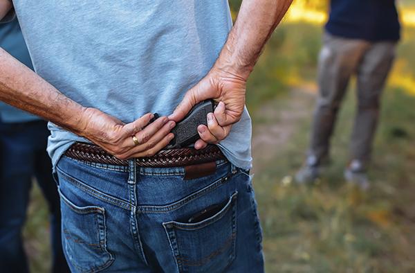 Man hides a hand gun behind his back under his belt