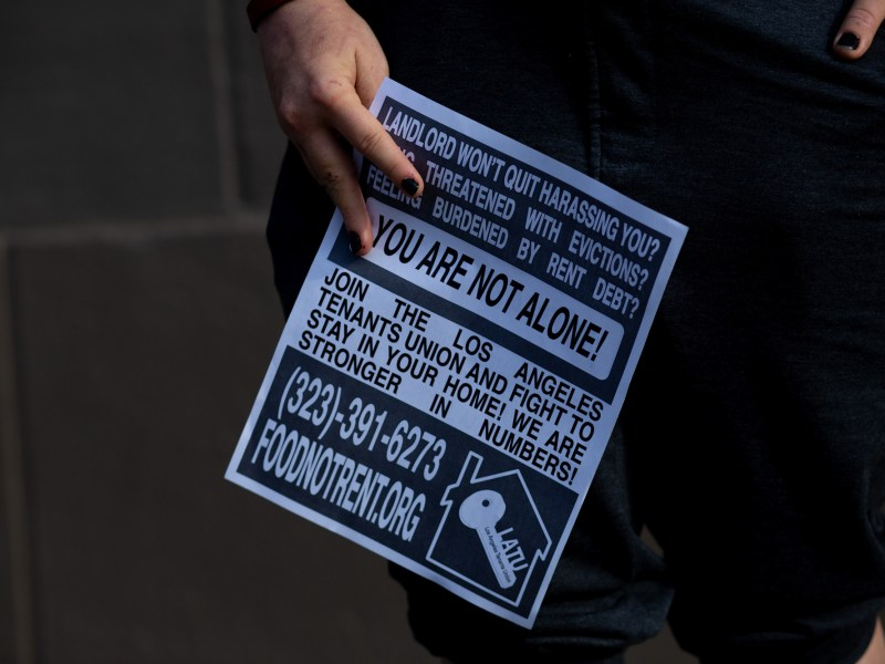 Jordan Lyric holds a rent strike poster in Los Angeles on May 6, 2021. Photo by Shae Hammond for CalMatters