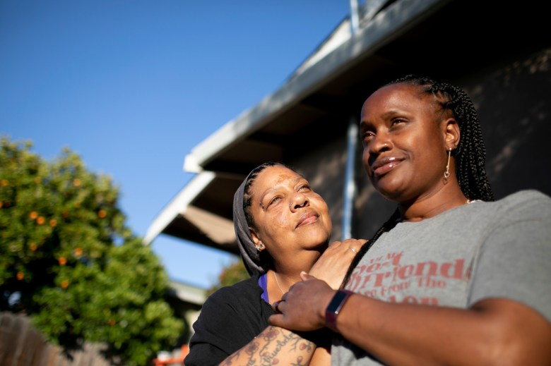 Esther Goolsby, left, and her fiancee, Merika Reagan, at their Oakland home on May 6, 2021. Reagan moved into the home in 2016 and through the Oakland Community land Trust can now work toward purchasing the property outright. Photo by Anne Wernikoff, CalMatters