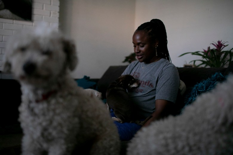 Merika Reagan plays with her dogs, Jordan, a chihuahua mix, and her two poodles, Goldie and Conseulo, in the living room of her Oakland home. Photo by Anne Wernikoff, CalMatters