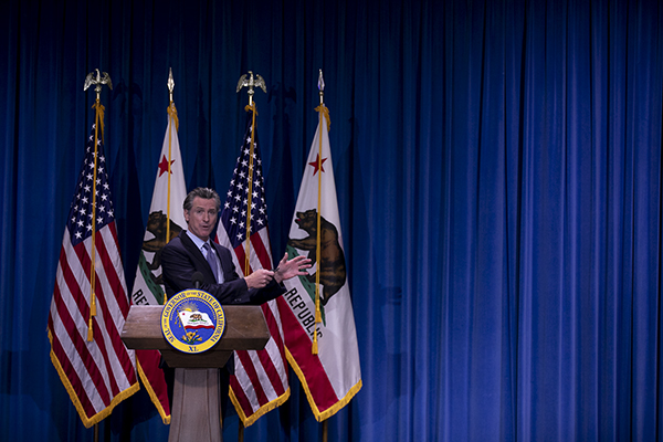 Gov. Gavin Newsom presents the breakdown for the $267.8 billion budget revise in a program dubbed 'California Roars Back' at the Secretary of State building auditorium in Sacramento on May 14, 2021. The budget focuses large allotments toward education, housing and climate resiliency measures. Photo by Anne Wernikoff, CalMatters