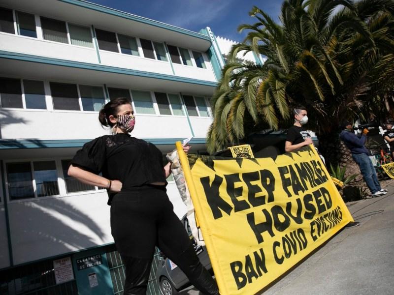 Los manifestantes sostienen una pancarta frente a un edificio de apartamentos en el vecindario Adams Point de Oakland para protestar por el pago de la renta y los desalojos durante la pandemia de coronavirus el 5 de diciembre de 2020. Foto de Anne Wernikoff para CalMatters
