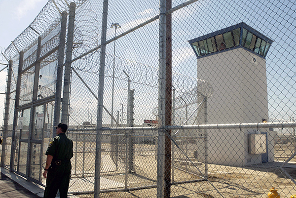 A correctional officer walks near a gate, which is one of two entrances into Kern Valley State Prison, in Delano, Calif in 2009. Photo by Ric Francis, AP Photo
