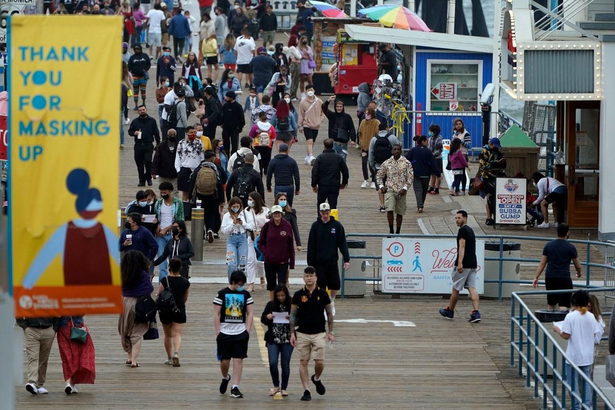Las personas con y sin máscaras caminan por el muelle de Santa Mónica el 13 de mayo de 2021. En el condado de Los Ángeles, aproximadamente el 45% de la población elegible, o un poco más de un tercio de toda la población del condado, estaba completamente vacunada la semana pasada. Foto de Marcio Jose Sanchez, AP Photo