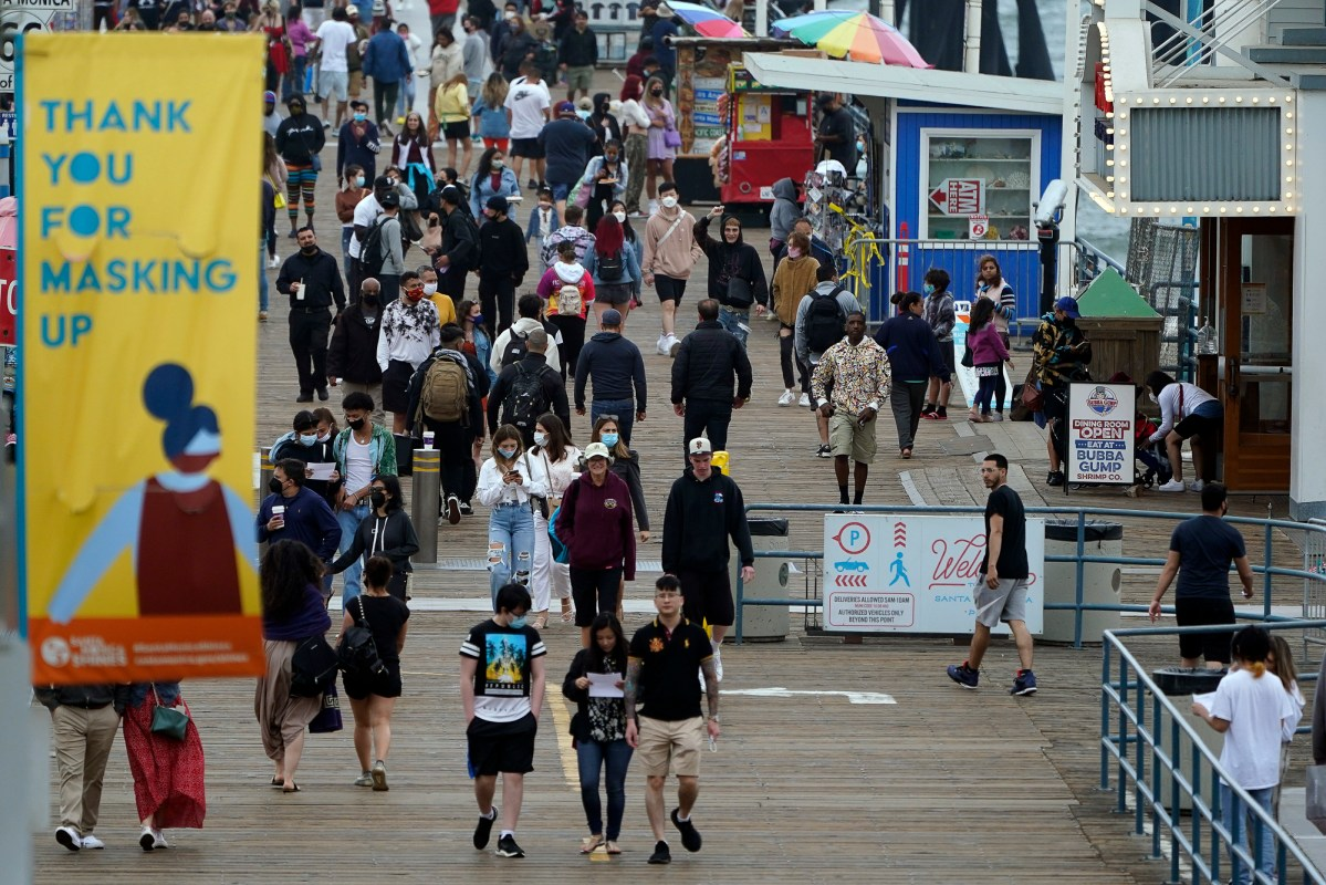 People with and without masks walk along Santa Monica Pier on May 13, 2021. In Los Angeles County, about 45% of the eligible population — or a little over a third of the entire county population — was fully vaccinated as of last week. Photo by Marcio Jose Sanchez, AP Photo