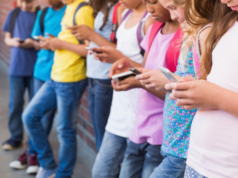 A row of children using smart phones. Advocates want California lawmakers to go further in regulating social media platforms. Image via iStock