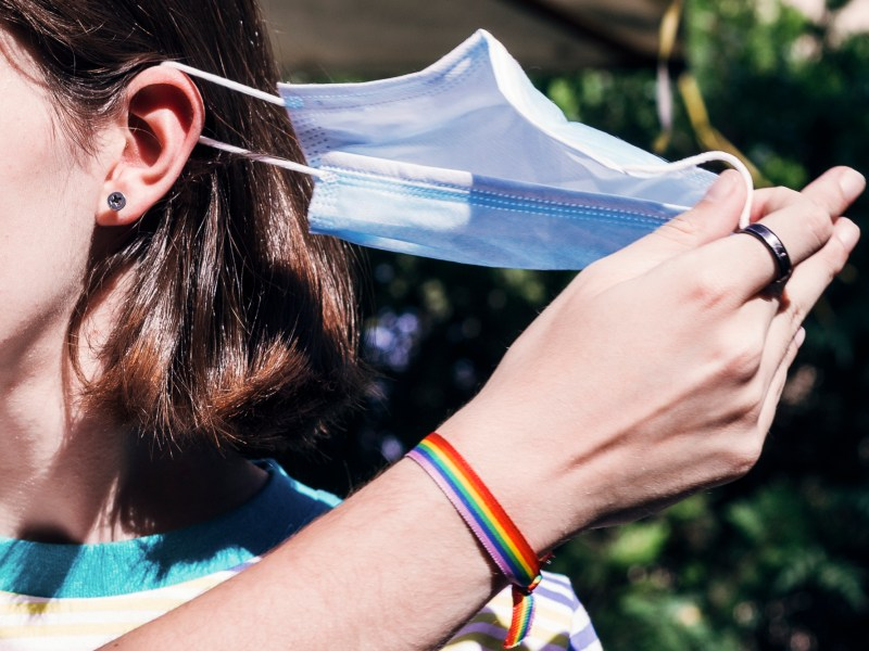 A teenage girl pulls a mask off her face. California will relax most mask restrictions by June 15. Image via iStock.