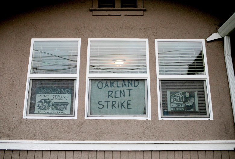 Rent strike signs are posted in the front window of an East Oakland home on May 6, 2021. Photo by Anne Wernikoff, CalMatters