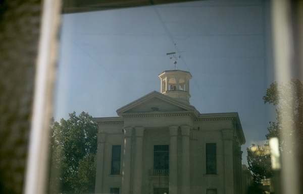 The Colusa courthouse reflected in the window of a nearby restaurant on May 25, 2021. Photo by Anne Wernikoff, CalMatters