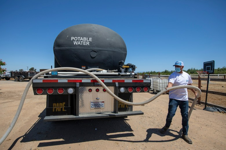 An employee from Bubba's Water Truck Service unravels a hose in preparation to pump water into Luzvianey Gonzalez's new home water tank in Madera on June 10, 2021. Photo by Shae Hammond for CalMatters