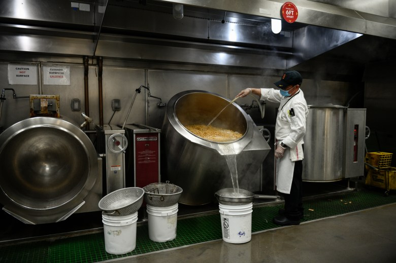 A Hospitality Training Academy participant drains pasta in an industrial kitchen at the Los Angeles Convention Center on June 14, 2021. The pasta will be prepared and sent out to home-bound seniors in Los Angeles County. Photo by Pablo Unzueta for CalMatters