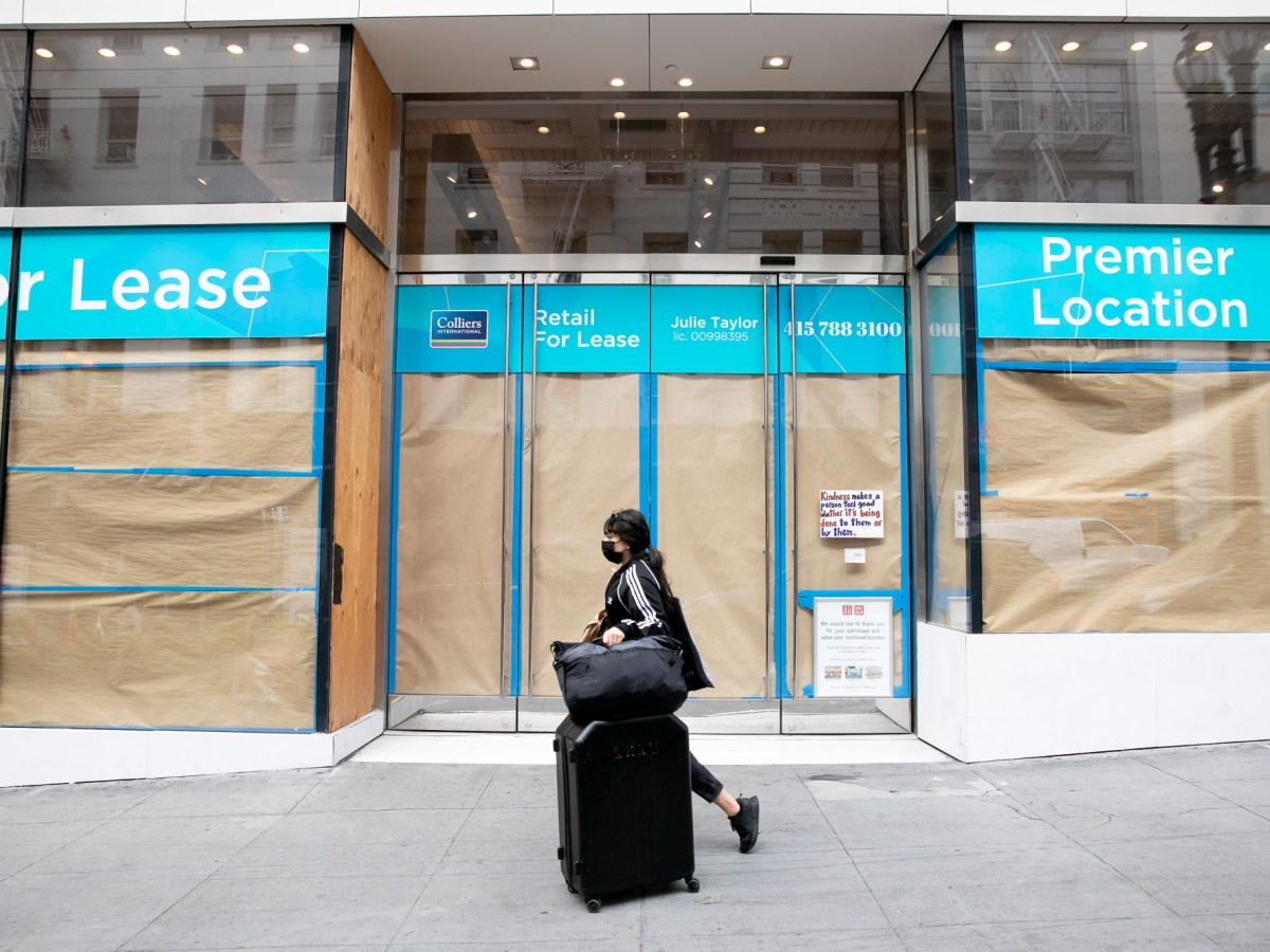 A pedestrian with a suitcase walks past a vacant store front on Powell Street in the Union Square shopping district in San Francisco on June 14, 2021. Photo by Anne Wernikoff, CalMatters