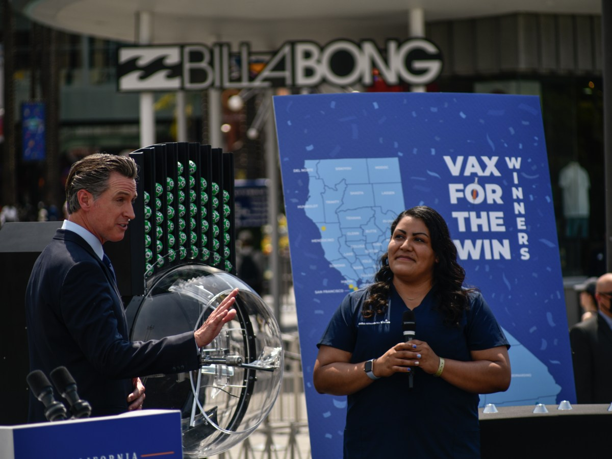 Gov. Gavin Newsom introduces Helen Cordova on stage, the first person in California to get the coronavirus vaccine, to celebrate California's reopening at Universal Studios in Universal City, on June 15, 2021. Photo by Pablo Unzueta for CalMatters