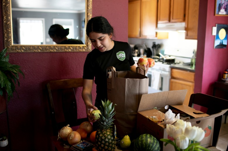 Claudeth unpacks free groceries and meals delivered by Oakland Unified School District. Photo by Anne Wernikoff, CalMatters