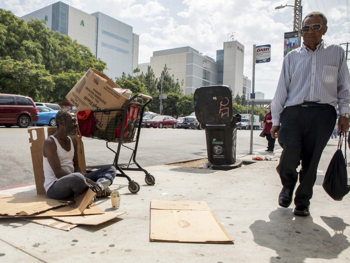 A man sits on the sidewalk across the street from LAC+USC Medical Center. He said he has been homeless since he arrived in Los Angeles from Chicago in 1982. Photo by Anne Wernikoff, CalMatters