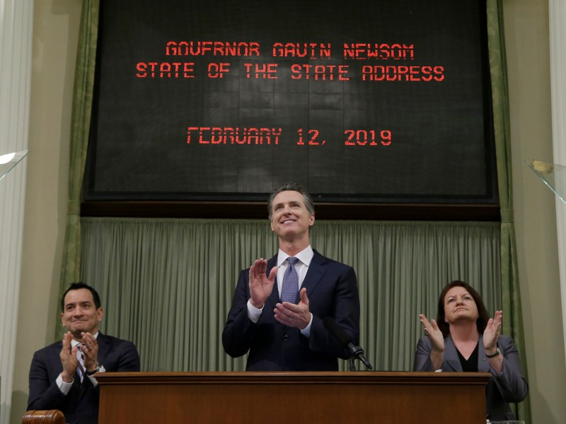 Gov. Gavin Newsom, center, flanked by Assembly Speaker Anthony Rendon, left, and Senate President Pro Tem Toni Atkins, right, applauds during his first State of the State address at the Capitol on Feb. 12, 2019. The three leaders announced a budget deal. Photo by Rich Pedroncelli, AP Photo