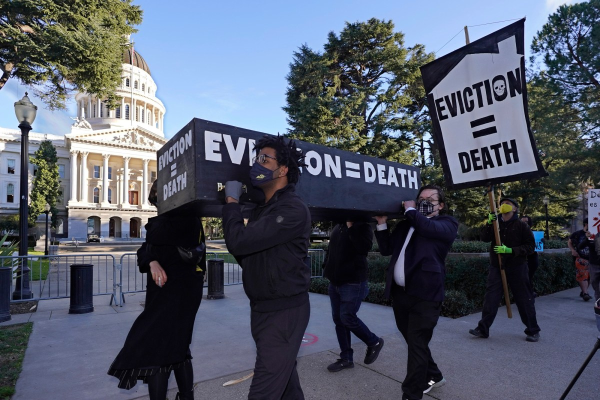 Demonstrators calling for California lawmakers and Gov. Gavin Newsom to pass rent forgiveness and a stronger eviction moratorium carry a mock casket past the Capitol in Sacramento on Jan. 25, 2021. Photo by Rich Pedroncelli, AP Photo
