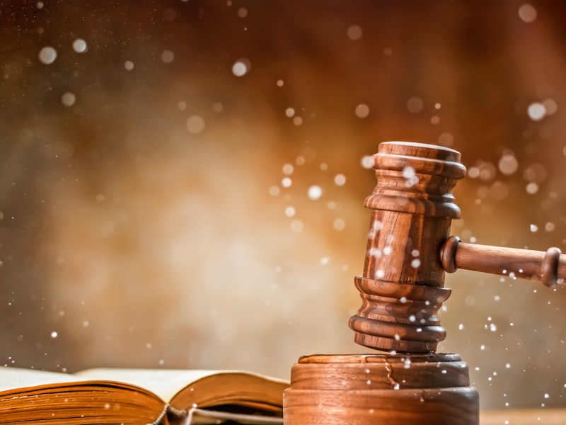 Wooden gavel with open law book. The California Supreme Court is expected to make a key death penalty ruling. Image via iStock