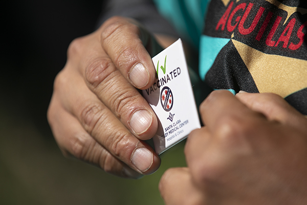 A fan puts on a 'vaccinated' pin after receiving the Johnson & Johnson vaccine during an event sponsored by the California Department of Public Health. Photo by Anne Wernikoff, CalMatters