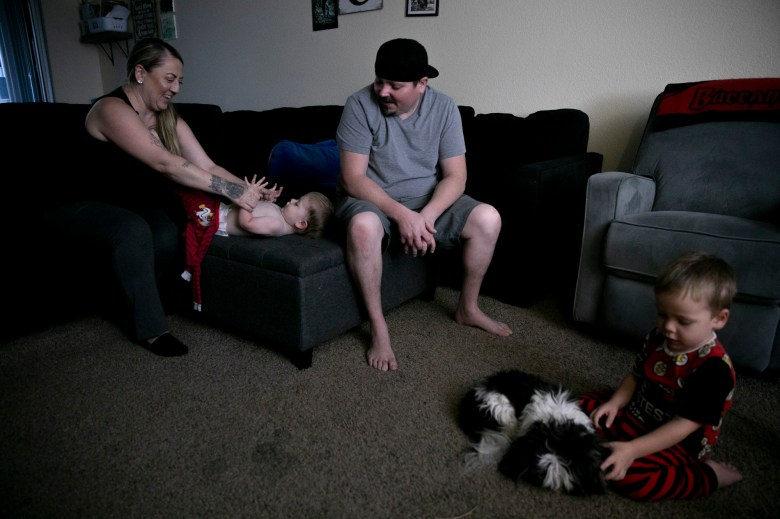 """Miranda Griswold dresses 23-month-old Jax for bed with her fiancé, Matt Calhoun, while three-year-old Rhys plays with the family dog at their Merced home on July 8, 2021. """"What are we doing to our families?"""" asked Griswold of the current family leave policy. """"There's no support."""" Photo by Anne Wernikoff, CalMatters"""