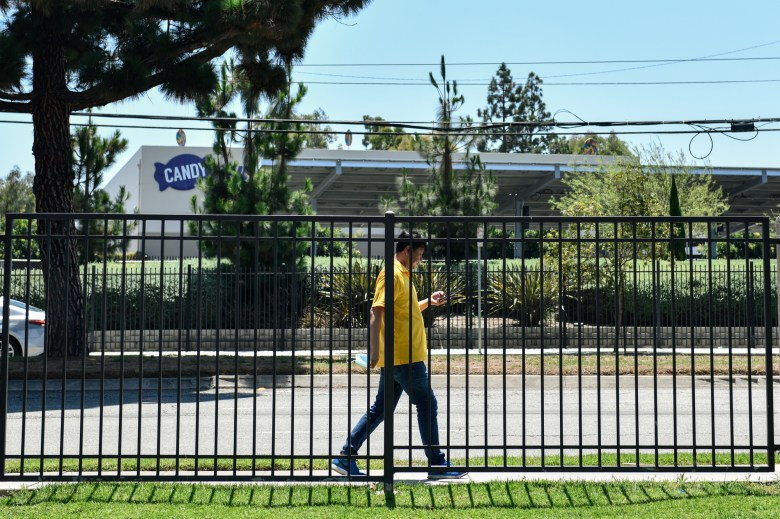 A man walks along a fence located near the Residence Inn by Marriott hotel in Long Beach, on July 30, 2021. The hotel is where Rasheena McCord and her children are temporarily living after she was evicted. Photo by Pablo Unzueta for CalMatters