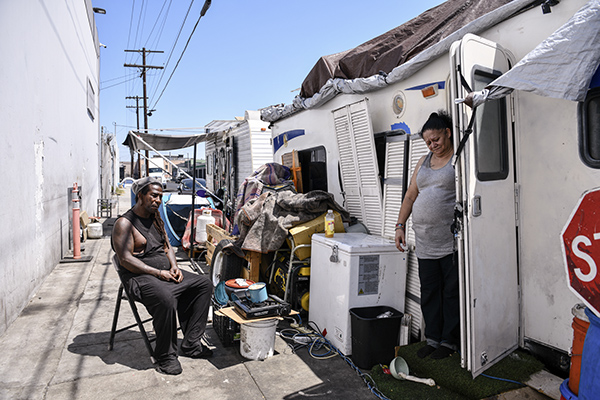 Rafael Suarez and April Lei outside of their trailer home try to stay cool during a hot day in Los Angeles, on July 9, 2021. The couple, who say they have lived on this block for a year and a half, try to keep their belongings organized in order to avoid sweeps. Pablo Unzueta for CalMatters