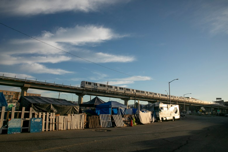 A tent community beneath BART tracks in West Oakland on Dec. 31, 2019. Photo by Anne Wernikoff, CalMatters