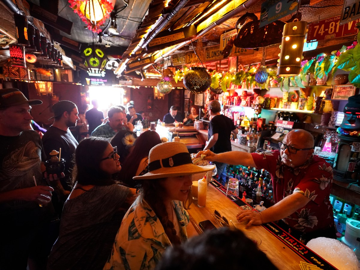 Maskless patrons enjoy tropical cocktails in the tiny interior of the Tiki-Ti bar as it reopens on Sunset Boulevard in Los Angeles on July 7, 2021. California COVID cases are climbing, especially in Los Angeles, just weeks after the state's broad reopening. Photo by /Damian Dovarganes, AP Photo
