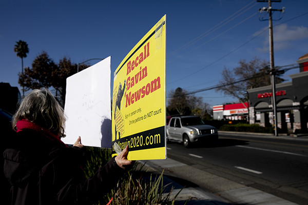 A recall supporter holds up a sign at a petition signing event in Sacramento on Jan. 5, 2021. Photo by Anne Wernikoff, CalMatters