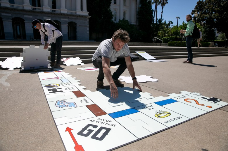 """Cox campaign staff set up a giant Monopoly board dubbed """"Gavinopoly"""" in front of the state capitol on Aug. 5, 2021. Photo by Anne Wernikoff, CalMatters"""