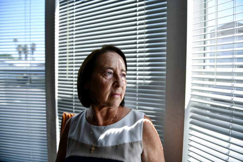 """Donna Shelden, a registered republican, looks out her window from her mobile home in Santa Ana on August 28, 2021. According to Sheldon, she will be voting to recall Gov. Gavin Newsom on Sept.14. """"I feel as though he is destroying the state,"""" Sheldon said. Photo by Pablo Unzueta for CalMatters"""