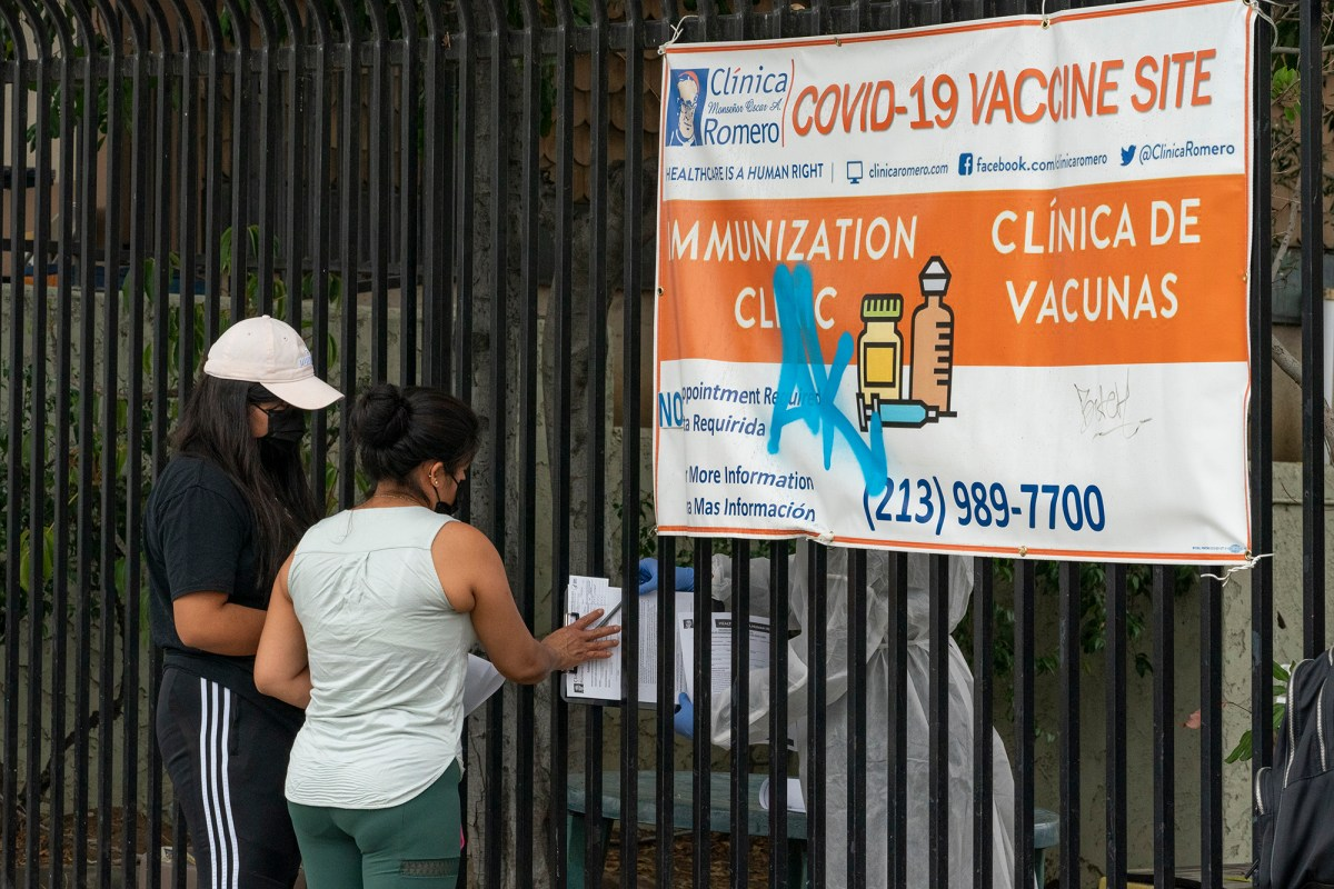People fill out forms before getting vaccinated at the Clínica Monseñor Oscar A. Romero in the Pico-Union district of Los Angeles, July 26, 2021. Photo by Damian Dovarganes, AP Photo