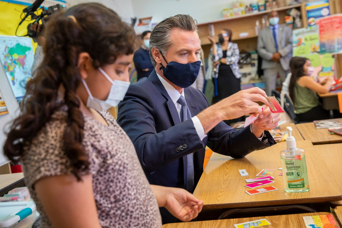 From left: Dina Kassan talks with California Gov. Gavin Newsom, who visited Carl B. Munck Elementary School, Wednesday, Aug. 11, 2021, in Oakland, Calif. The governor announced that California will require its 320,000 teachers and school employees to be vaccinated against the novel coronavirus or submit to weekly COVID-19 testing. Photo by Santiago Mejia, San Francisco Chronicle, Pool