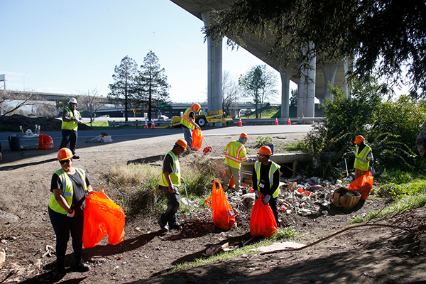 Caltrans contractors clear out garbage left behind at a homeless camp under the Highway 101-280 interchange after it was cleared by the California Highway Patrol in 2017 in San Jose. Photo by Karl Mondon, Bay Area News Group
