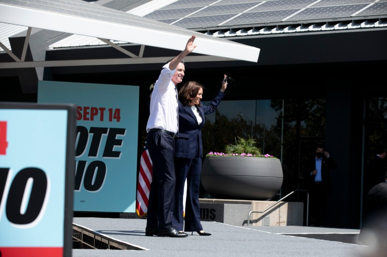 """Gov. Gavin Newsom and Vice President Kamala Harris embrace on stage during a campaign rally encouraging Californians to vote """"no"""" on the recall election next week, at the IBEW-NECA training center in San Leandro on Sept. 8, 2021. Newsom faces the recall election next week. Photo by Anne Wernikoff, CalMatters"""