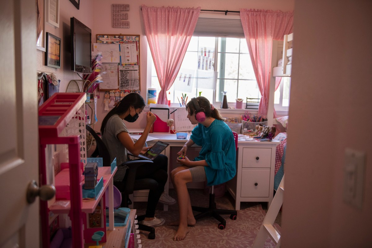 """Ellie sits in her room with a behavioral therapist during class time in Monrovia, on Sept. 15, 2021. """"There is no way to go back with 37 kids in a classroom,"""" Julie Fitzgibbons, the mother of triplets, said. """"With masks and not being able to communicate very well, and autism, there is just no way we can go back like normal."""" Photo by Pablo Unzueta for CalMatters"""